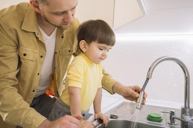 Padre lavando los platos y su hijo está mirando