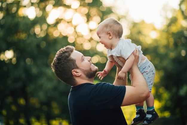 Padre levantando a su hijo en el aire.