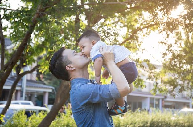 Padre levantando a su hijo en la mano y pretendiendo rodar con placer en desenfoque en el jardín