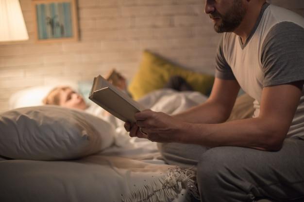 Padre leyendo cuento antes de dormir a hijo