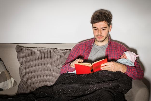 Padre con el libro de lectura del bebé en la noche