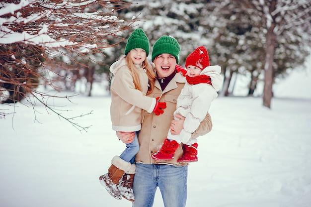 Padre con lindas hijas en un parque de invierno