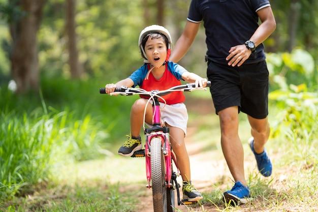 El padre lleva a los niños a practicar ciclismo.