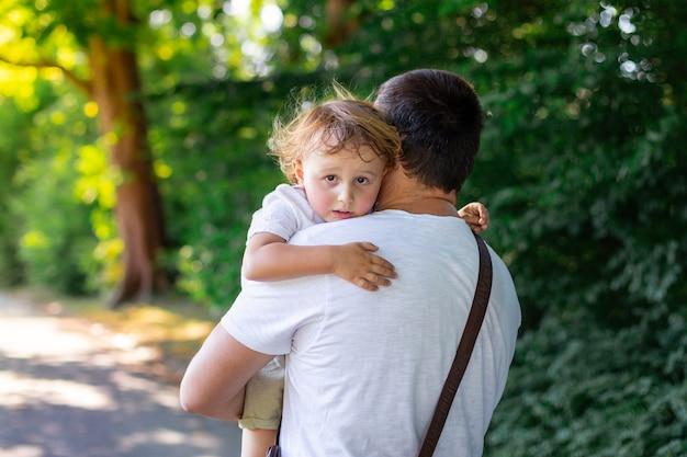 El padre lleva a su pequeño hijo cansado después de un largo paseo por un parque en verano. niño pequeño exhausto soñoliento descansando en los brazos de papá.