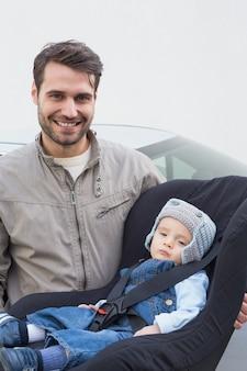 Padre llevando bebé en su asiento de coche
