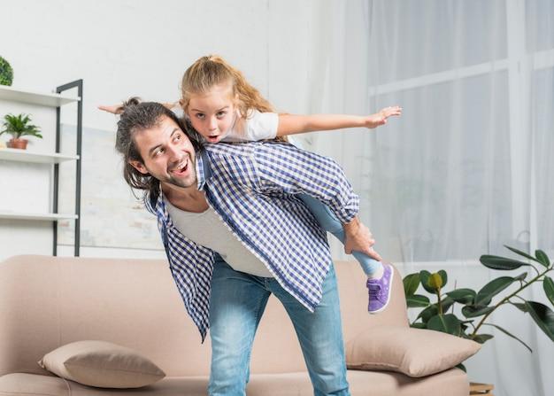 Padre llevando a caballito a su hija