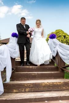Padre llevando a la novia sonriente feliz al altar de bodas bajando las escaleras