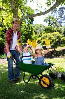 Padre llevando a su hijo e hija en una carretilla de mano