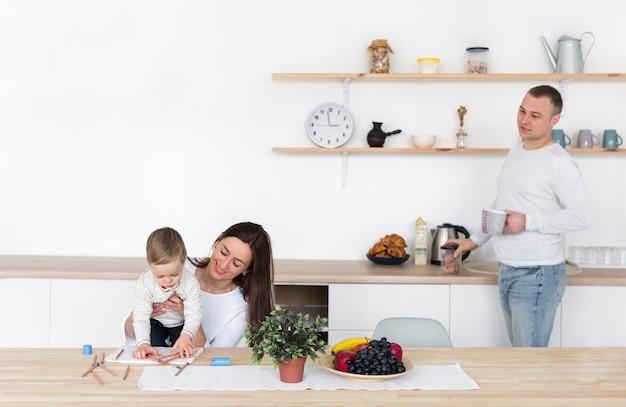 Padre y madre en la cocina con niño y espacio de copia