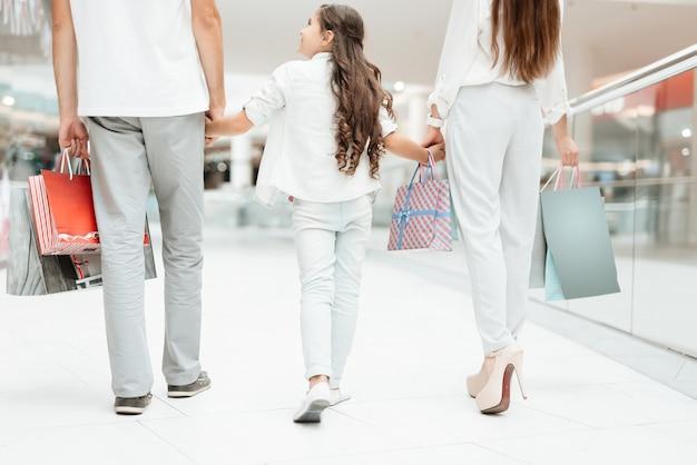 Padre, madre e hija están caminando en el centro comercial
