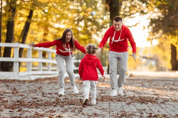 Padre, madre e hija están caminando en el parque de otoño, la familia feliz se divierte al aire libre.