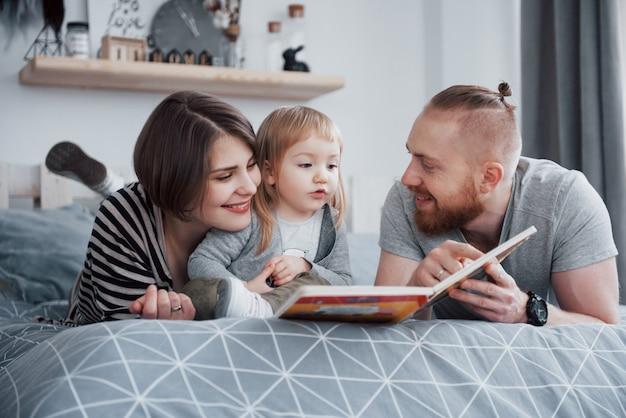 Padre, madre e hija leyendo el libro infantil en un sofá en la sala de estar. la gran familia feliz leyó un libro interesante en un día festivo. los padres aman a sus hijos