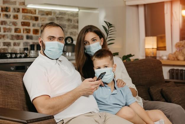 Padre, madre e hijo están sentados en un sofá con mascarillas médicas para evitar la propagación del coronavirus (covid-19).