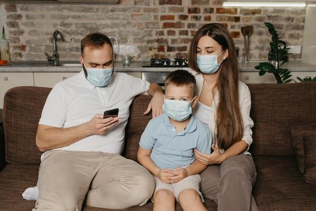Padre, madre e hijo están sentados en un sofá con mascarillas médicas para evitar la propagación del coronavirus (covid-19)