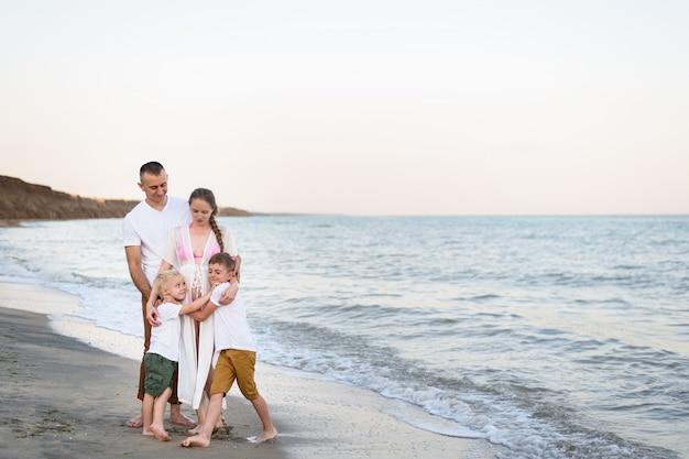 Padre, madre embarazada y dos hijos en la costa del mar.