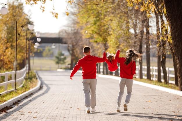 El padre y la madre están sosteniendo a la pequeña hija de las manos y caminando en el parque de otoño, la familia feliz se divierte al aire libre.