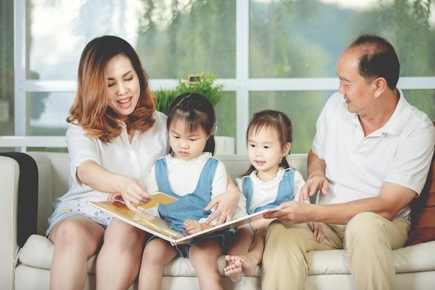 Padre y madre leyendo un libro de dibujos animados a su hija.