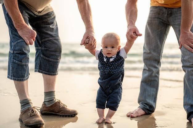 Padre y madre llevan a su hijo de la mano a dar un paseo por la playa por la noche