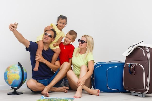 Padre, madre, niño y niña sentados junto a las maletas y el globo terráqueo, tomando selfie antes del viaje.