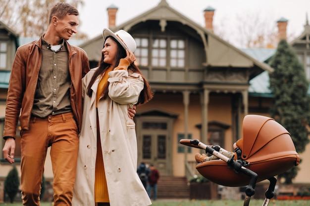 Padre y madre en un paseo con un cochecito en otoño. una familia pasea por el parque natural de otoño dorado.