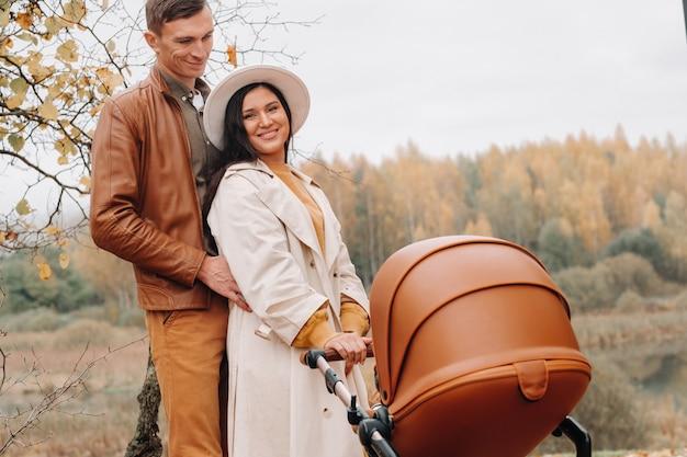 Padre y madre en un paseo con un cochecito en el parque de otoño. la familia pasea por el parque natural en el otoño dorado.