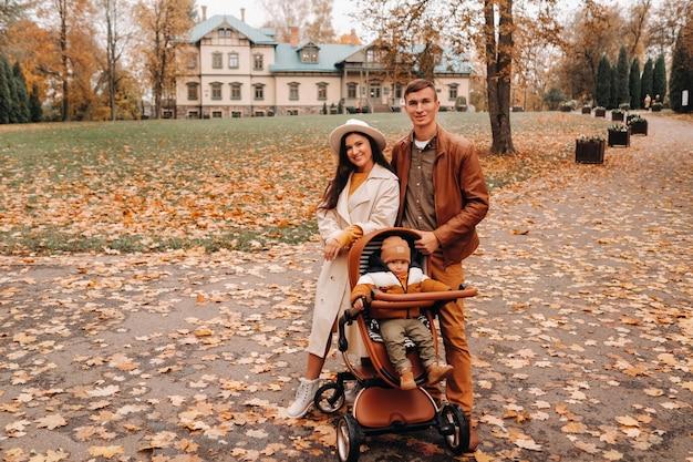Padre y madre en un paseo con un niño en un cochecito en el otoño parque en el fondo de la finca. una familia pasea por el parque natural de otoño dorado.