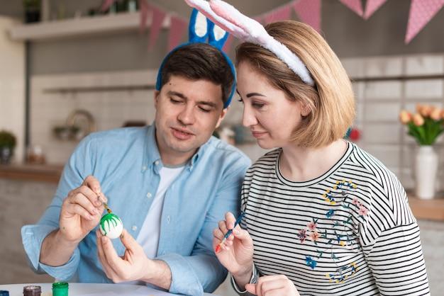 Padre y madre pintando huevos para pascua