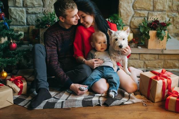Padre y madre con su bebé y el perro sentados en el suelo