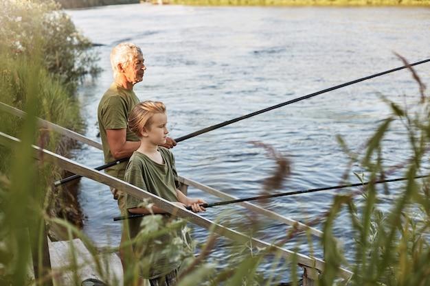 Padre maduro de pelo gris europeo con hijo pescando al aire libre en el lago o río, de pie cerca del agua con cañas de pescar en las manos, vestido informal, disfrutando de la afición y la naturaleza.