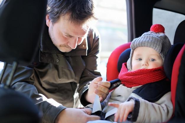 El padre de mediana edad ayuda a su hijo pequeño a abrocharse el cinturón en el asiento del auto