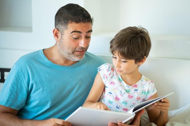 Padre de mediana edad con su hija de ocho años usando tableta digital en el dormitorio.
