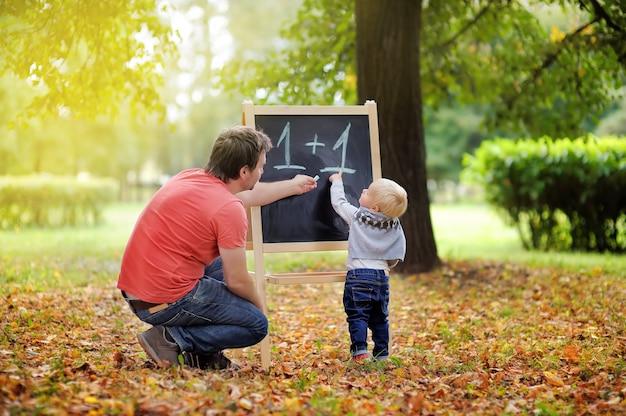 Padre de mediana edad y su hijo pequeño en la pizarra practicando matemáticas