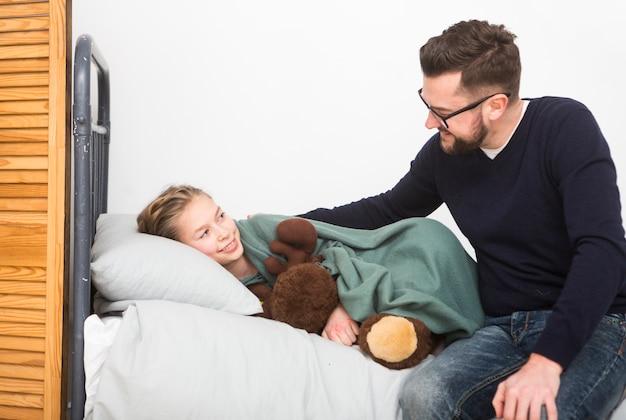 Padre metiendo hija en cama