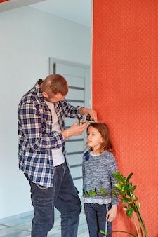 El padre mide la altura de la hija contra la pared en casa
