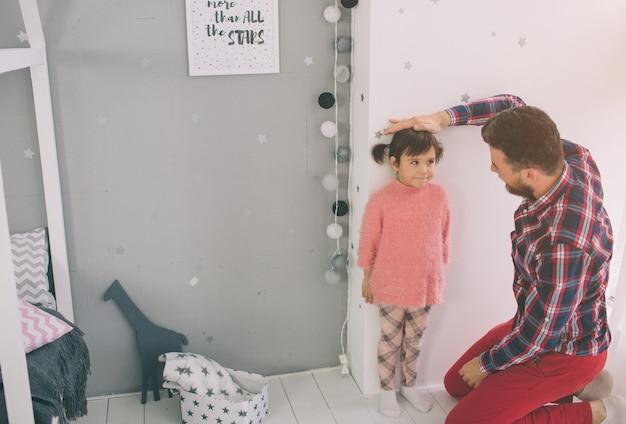 Padre está midiendo la altura de su bebé en la pared. linda hijita y su apuesto joven papá están jugando juntos en la habitación del niño