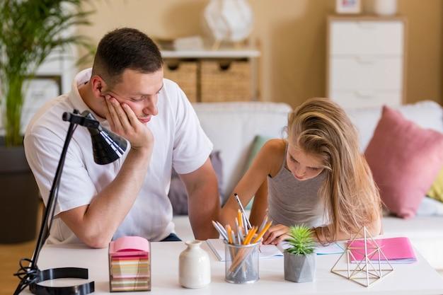 Padre mirando los dibujos de su hija.