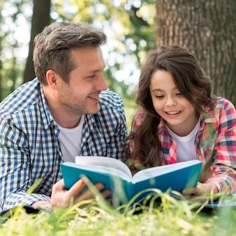 Padre mirando a su hija mientras lee un libro en el parque