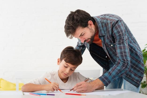 Padre mirando a su hijo haciendo la tarea