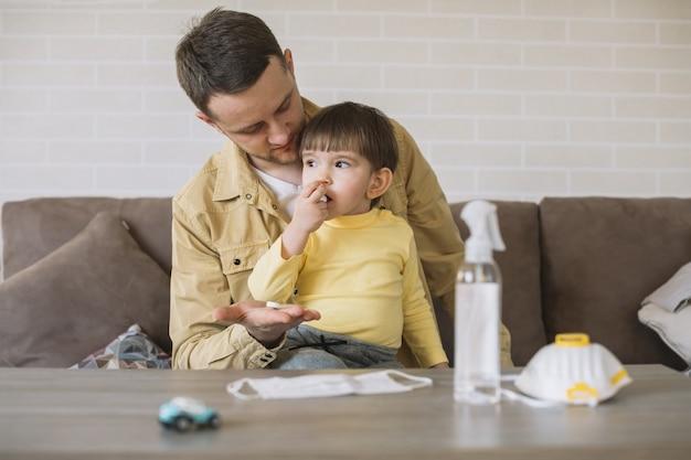Padre mirando a su hijo y máscara médica en mesa