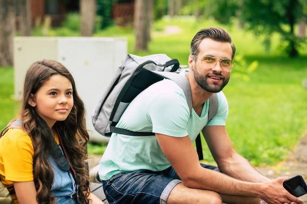 Padre con mochila gris e hija pequeña