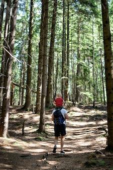 Padre con mochila y joven hijo sobre sus hombros caminando sobre un bosque de coníferas. vista trasera. actividades y turismo
