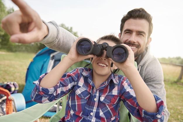 Padre mostrando a su hijo el mundo a través de binoculares