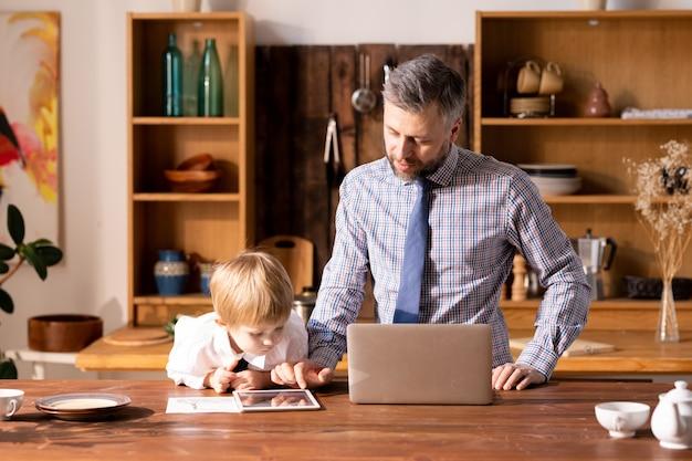 Padre mostrando tableta a hijo