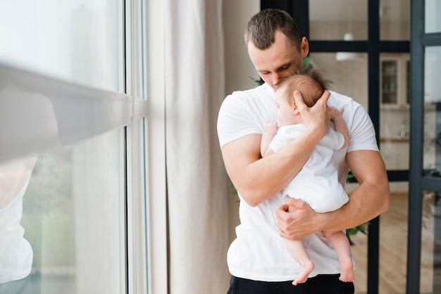 Padre musculoso de pie y sosteniendo bebe