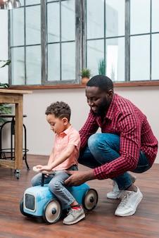Padre negro ayudando a su hijo con el coche de juguete de conducción