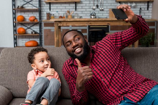 Padre negro e hijo tomando selfie mostrando los pulgares para arriba