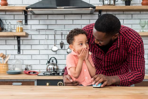 Padre negro hablando con hijo asombrado