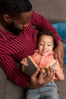 Padre negro y libro de lectura lindo del hijo en el sofá