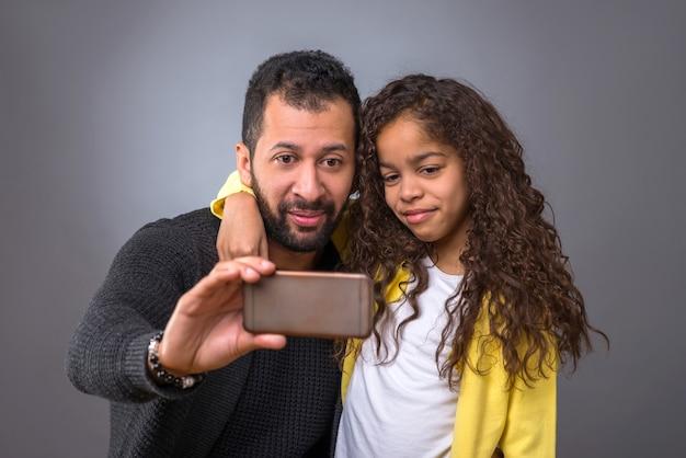 Padre negro tomando selfies con su hija