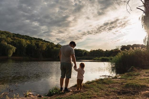 Padre y niña sentada cerca del lago. viaje local. nuevas vacaciones normales. dia del padre